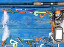Articles de pêche - pêche tournant, ligne de pêche, crochets, navigateur et bobine sur le fond en bois bleu Photographie stock