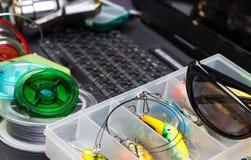 Articles de pêche sur le clavier un carnet noir Photographie stock