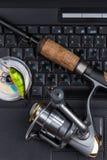Articles de pêche sur le clavier un carnet noir Photos stock