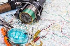 Articles de pêche - tige, bobine, ligne et attrait sur la carte Photos stock