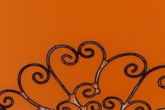 Articles forgés sur les portes grises en métal Articles forgés sur le fond orange Photo conceptuelle images stock
