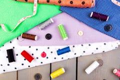 Articles pour les vêtements de couture Boutons de couture, bobines de fil et tissu Vue supérieure Images libres de droits