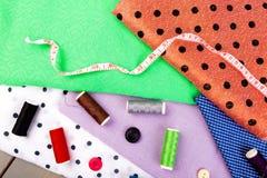 Articles pour les vêtements de couture Boutons de couture, bobines de fil et tissu Vue supérieure Photo stock