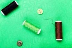 Articles pour les vêtements de couture Boutons de couture, bobines de fil et tissu Vue supérieure Photos stock