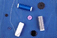 Articles pour les vêtements de couture Boutons de couture, bobines de fil et tissu Vue supérieure Image stock