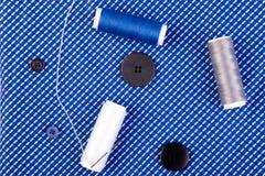 Articles pour les vêtements de couture Boutons de couture, bobines de fil et tissu Vue supérieure Images stock
