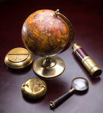 Articles of seaman. Globe, spyglass, ash-tray lie on a wooden table Royalty Free Stock Photos