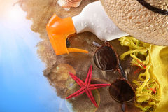 Articles for sun protection on sand on blue table top Stock Photos