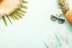 Articles ?tendus plats de voyage : ananas, chapeau de paille, fleur, lunettes de soleil, pantoufles de plage et palmette frais Pl photo stock