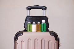 Articoli da toeletta di viaggio, piccole bottiglie di plastica dei prodotti di igiene sulla valigia Immagini Stock