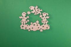 Articoli di legno, angeli di Natale sulle nuvole con le stelle su un fondo verde fotografia stock