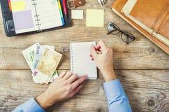 Articoli per ufficio, aggeggi e soldi sulla tavola di legno Fotografia Stock Libera da Diritti