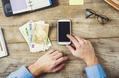 Articoli per ufficio, aggeggi e soldi sulla tavola di legno Immagini Stock Libere da Diritti