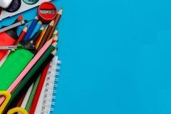 Articoli per ufficio della scuola su fondo blu immagini stock libere da diritti