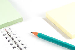 Articoli per ufficio - matita della grafite sul taccuino e sulla carta per appunti bianchi di colore Immagini Stock Libere da Diritti