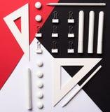 Articoli per ufficio sulla tavola rossa e nera bianca del fondo Immagine Stock