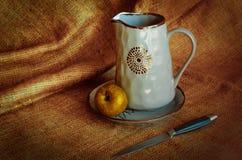 Articolo da cucina per i paesani Nutrmort con le brocche, una mela e un coltello Fondo caldo del tessuto Toni di autunno Stile ru fotografia stock libera da diritti
