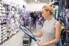 Articolo sportivo di acquisto della donna nel deposito degli abiti sportivi Fotografie Stock
