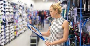 Articolo sportivo di acquisto della donna nel deposito degli abiti sportivi Fotografia Stock