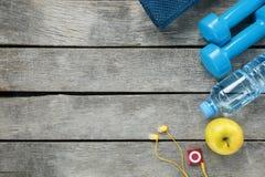 Articolo sportivo su un fondo grigio e di legno, teste di legno, acqua in una bottiglia, giocatore della mela immagine stock libera da diritti