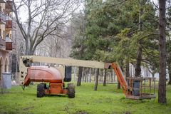 Articulated Boom Lift in the grass in a park. royalty free stock photos