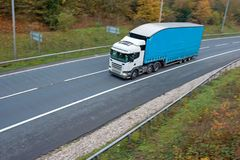 Articulated lorry on the road. Articulated lorry with blue high double decker trailer in motion on the road royalty free stock images