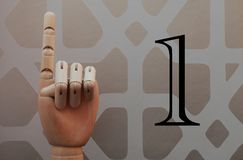 Articulated wooden hand with a finger raised in allusion to number one. On a background of vintage style wallpape Royalty Free Stock Photography