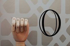 Articulated wooden hand with no raised finger in allusion to number zero. On a background of vintage style wallpaper Stock Photo