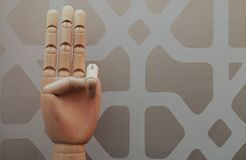 Articulated wooden hand with three fingers raised in allusion to number three. On a background of vintage style wallpaper Stock Photography