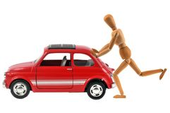 Articulated wooden mannequin pushing a broken down car on white background. Car breakdown concept close up on white background stock photo