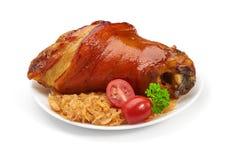 Articulation de porc avec la choucroute et les légumes frits Photographie stock libre de droits