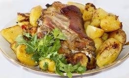 Articulation de porc cuite au four avec des pommes de terre Photographie stock
