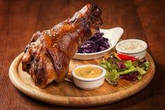 Articulation rôtie de porc avec le chou, le raifort et la moutarde bouillis sur le fond en bois Photo libre de droits