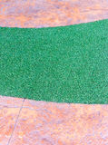 Artifical grass strip in the stone pathway. Royalty Free Stock Photo