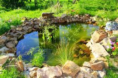 Artificial beautiful pond with rich vegetation and stones on a sunny day in summer stock photography