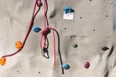 Artificial boulder climbing wall. Knotted rope on an artificial boulder climbing wall Stock Photo