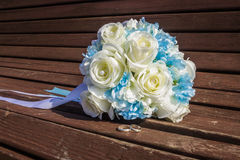 Artificial bouquet of white roses and wedding rings are on the bench Stock Photography