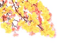 Artificial branch with yellow and pink flowers. Royalty Free Stock Images