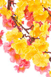 Artificial branch with yellow and pink flowers. Stock Image