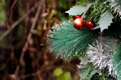 Artificial Christmas tree branch with a ball on a blurred background Stock Images