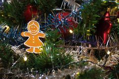 Artificial christmas tree decorated with wooden figurine, decoration for christmas tree, lights, tinsel and garland, red balls royalty free stock photography