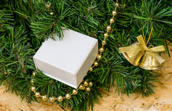 Artificial Christmas tree, golden beads and bell, a gift in a wh Stock Photography