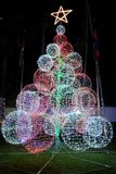 Artificial Christmas tree with a large glowing star at the top. Large glowing balls. New Year decoration.  stock photos