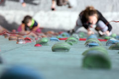 Artificial Climbing wall holds and blurred climbers Stock Images