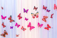 The artificial colorful butterflies on colorful curtain background. The butterflies fly one by one in a curve. royalty free stock image