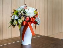 Artificial colorful flower in white ceramic container on wooden Stock Photos