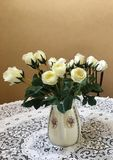 Artificial cream color rose flowers in ceramic vase on white lace tablecloth in retro style royalty free stock photo