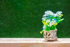 Artificial de la flor colorida en un florero viejo en la tabla de madera - S Imagen de archivo