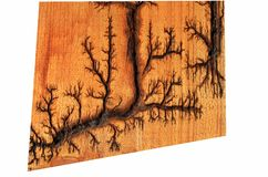 The artificial drawing of a lightning on a tree. The lightning drawn with electric current on a wooden board royalty free stock photo