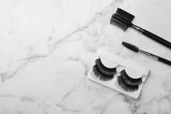 Artificial eyelashes and accessories on marble background, top view. With space for text royalty free stock photography